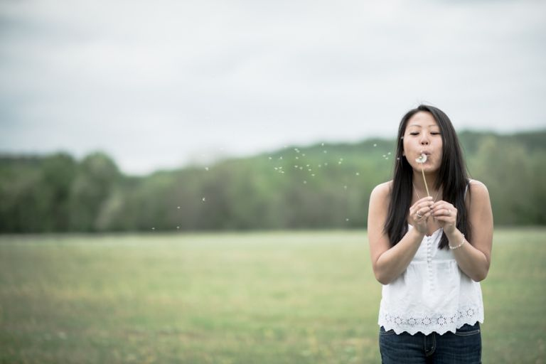 Kelly blows on dandelions during her engagement session in Hunterdon, NJ. Captured by awesome NJ wedding photographer Ben Lau.