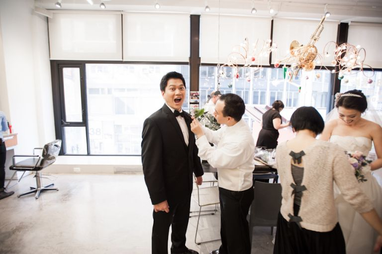 The groom gestures towards the camera on his wedding day. Captured by awesome New York City wedding photographer Ben Lau.
