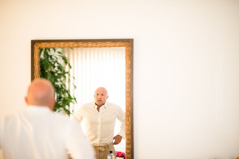 Groom gets ready in front of a mirror before his wedding ceremony at the CuisinArt Resort & Spa in Anguilla. Captured by Caribbean destination wedding photographer Ben Lau.