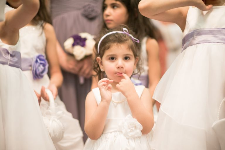Flower girl looks at the camera during a wedding ceremony in Jersey City, NJ. Captured by awesome NJ wedding photographer Ben Lau.