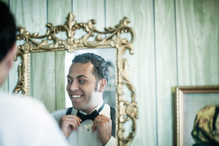 Groom Sam gets ready in front of a mirror on his wedding day in Jersey City, NJ. Captured by awesome New Jersey wedding photographer Ben Lau.