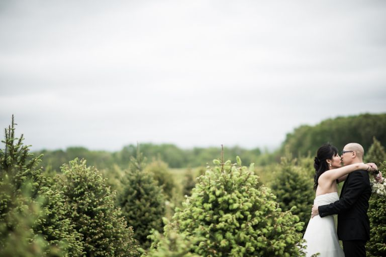 Bride and groom share a kiss in a field of trees on their wedding day in Princeton, NJ. Captured by awesome NJ wedding photographer Ben Lau.