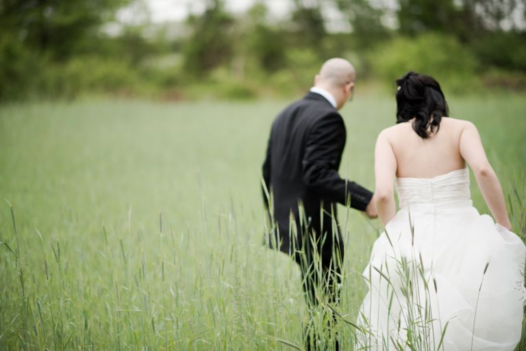 Groom leads his bride into a field of grass on their wedding day in Princeton, NJ. Captured by awesome NJ wedding photographer Ben Lau.