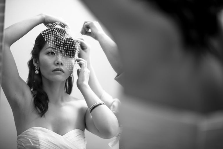 Bride prepares her headpiece on her wedding day at the Mountain Lakes House in Princeton, NJ. Captured by awesome New Jersey wedding photographer Ben Lau.
