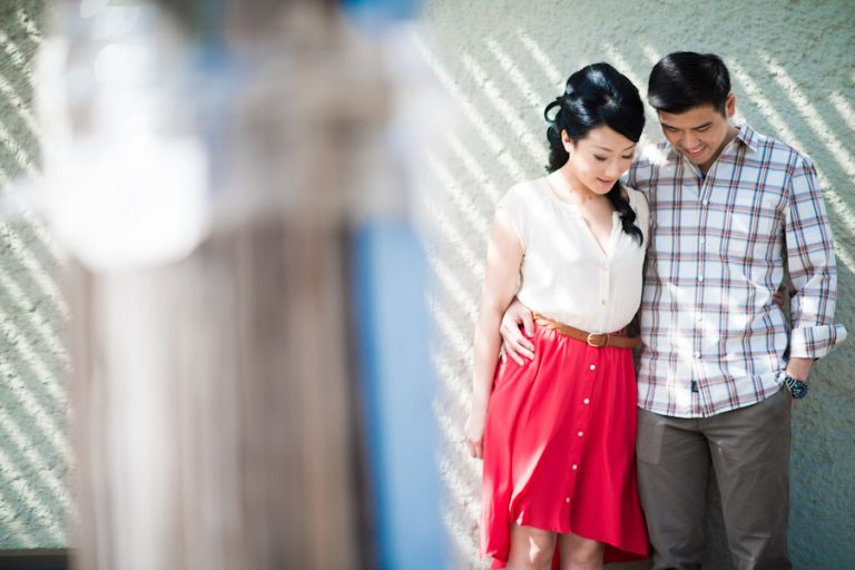 Yumi and Alan pose along a wall in Vinegar Hill during their engagement session with awesome NY wedding photographer Ben Lau.