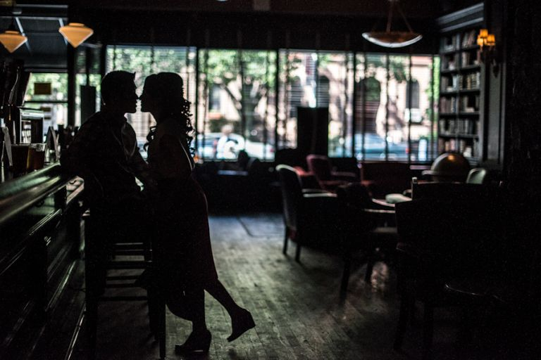 Yumi and Alan pose inside a bar in Brooklyn NY during their engagement session.