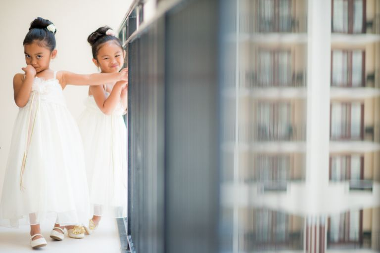 Flower girls play during bridal prep before a wedding at the Oxon Hill Manor in Oxon Hill, MD. Captured by awesome NJ wedding Photographer Ben Lau.