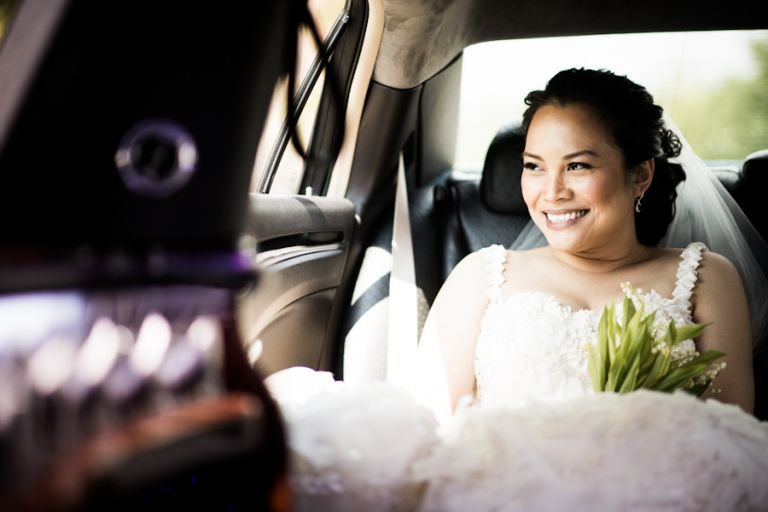 Bride looks out of the window of her limo while en route to her wedding reception at the Oxon Hill Manor in Oxon Hill, MD. Captured by awesome NJ wedding Photographer Ben Lau.