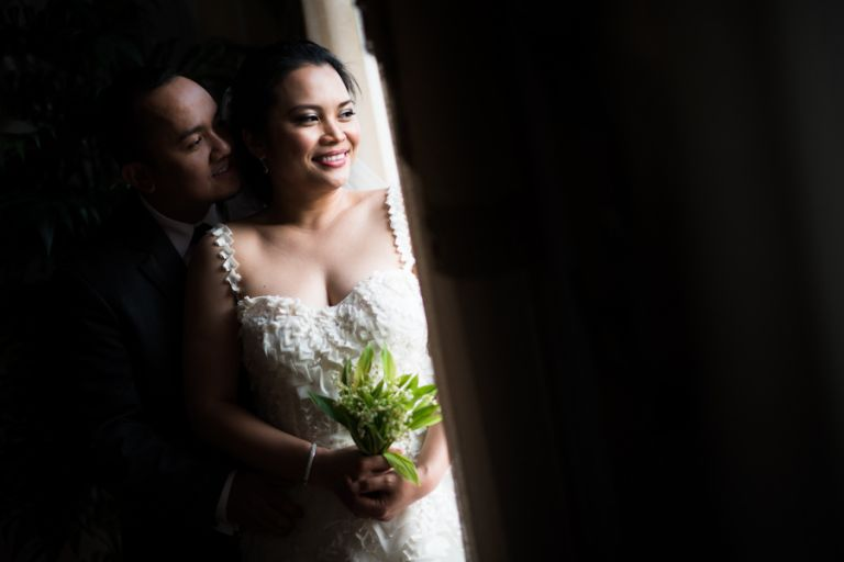 Bride and groom pose near a window at the Oxon Hill Manor in Oxon Hill, MD. Captured by awesome NJ wedding Photographer Ben Lau.