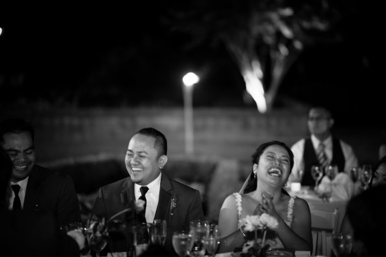 Bride and groom laugh during speeches at their wedding at the Oxon Hill Manor in Oxon Hill, MD. Captured by awesome NJ wedding Photographer Ben Lau.