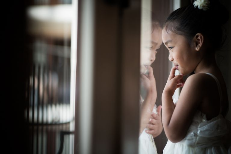 Flower girl looks out window during prep at the Gaylord National Resort in Washington DC. Captured be awesome NJ wedding photographer Ben Lau.