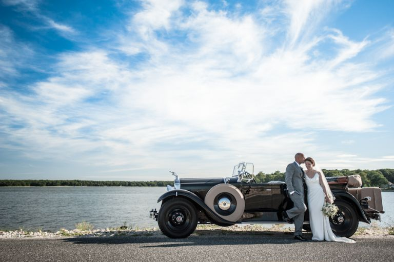 Bride and groom stand by their antique car on the causeway, en route to their wedding reception at the Rams Head Inn on Shelter Island, NY.