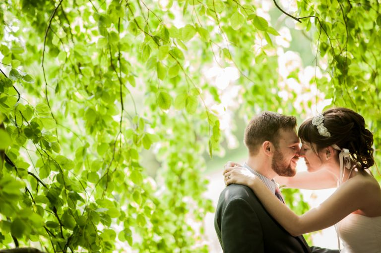 Bride and groom pose together on their wedding day at the Bayard Cutting Arboretum on Long Island, NY. Captured by awesome NJ wedding photographer Ben Lau.