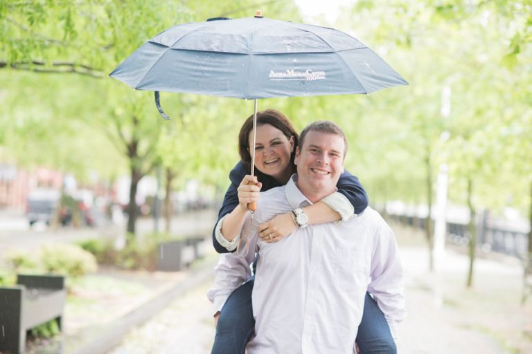 Piggy back ride under an umbrella during a rainy engagement session in Hoboken, NJ. Captured by awesome NJ wedding photographer Ben Lau.