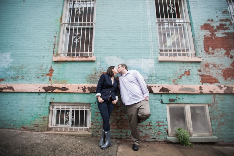 Couple poses against a wall during a rainy engagement session in Hoboken, NJ. Captured by awesome NJ wedding photographer Ben Lau.