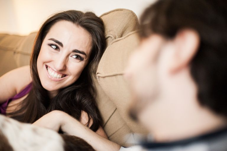 Margot and Alex lay on their couch with Baby Girl during their engagement session in their Upper East Side apartment with awesome NY wedding photographer Ben Lau.