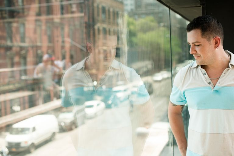 Brian poses by a window during their engagement session in the Meatpacking District with awesome NJ wedding photographer Ben Lau.