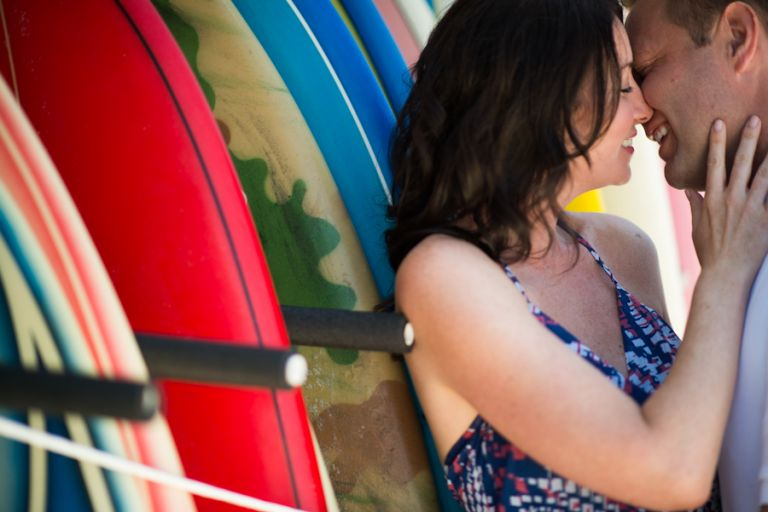 Nicole and Gregg kiss on a row of surfboards in Long Beach Island, NJ during their engagement session with Ben Lau Photography.