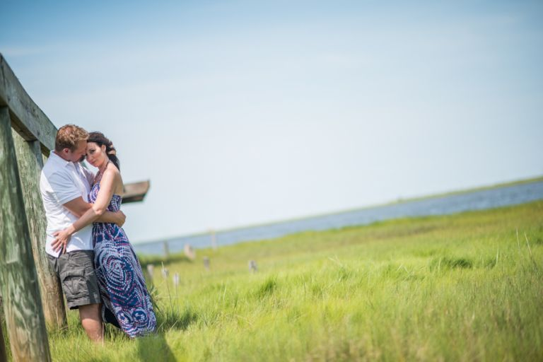 Nicole and Gregg kiss on an old pier in a marsh in Long Beach Island, NJ during their engagement session with Ben Lau Photography.