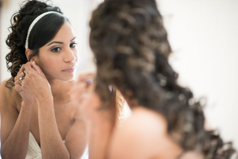 Bride puts on her earrings on her wedding day at The Manor in West Orange, NJ. Captured by awesome NJ wedding photographer Ben Lau.