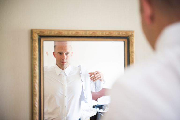 Groom puts on his jacket on his wedding day at The Manor in West Orange, NJ. Captured by awesome NJ wedding photographer Ben Lau.
