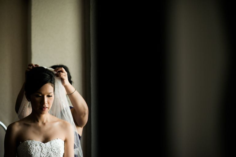 Bride puts on her veil on her wedding day. Captured by Montreal, QC wedding photographer Ben Lau.