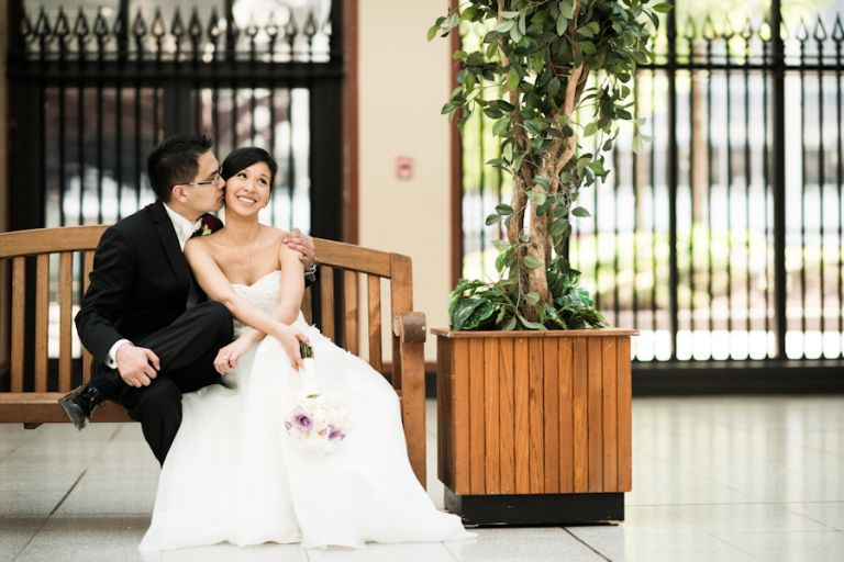 Bride and groom pose on a bench on their wedding day. Captured by Montreal, QC wedding photographer Ben Lau.