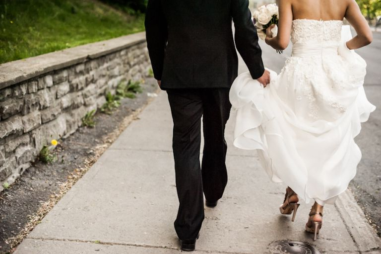 Bride and groom walk on the sidewalk. Captured by Montreal, QC wedding photographer Ben Lau.