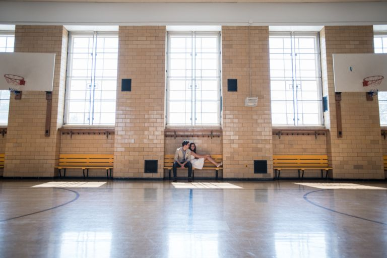 Christina and Nick pose inside an elementary school gymnasium for the engagement session with New York City Wedding photographer Ben Lau.