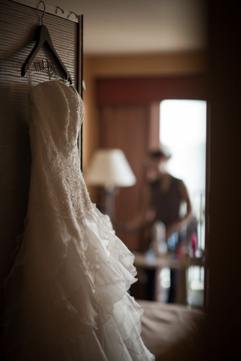 Bride's wedding dress hangs in her room before her ceremony at Herrington on the Bay in Chesapeake Beach, MD. Captured by NJ wedding photographer Ben Lau.