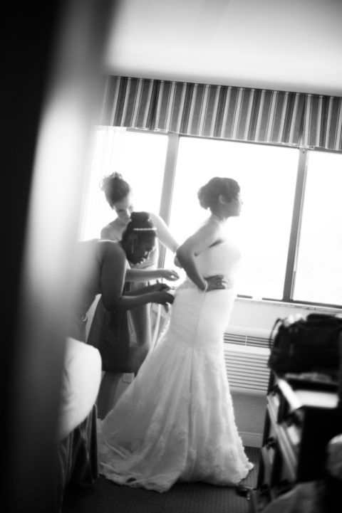 Bride puts on her dress before her wedding at the Coral House in Baldwin, NY. Captured by awesome NJ wedding photographer Ben Lau.