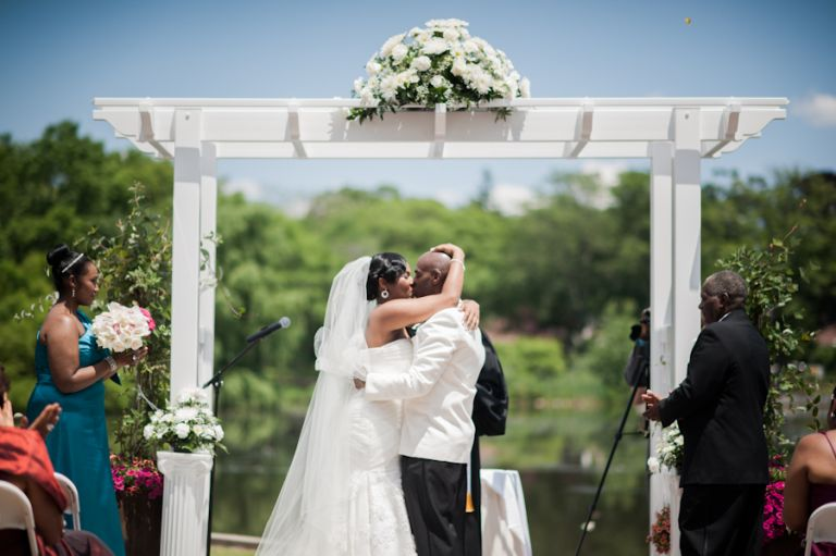 Bride and groom share a kiss near the pond at Coral House in Baldwin, NY. Captured by awesome NJ wedding photographer Ben Lau.