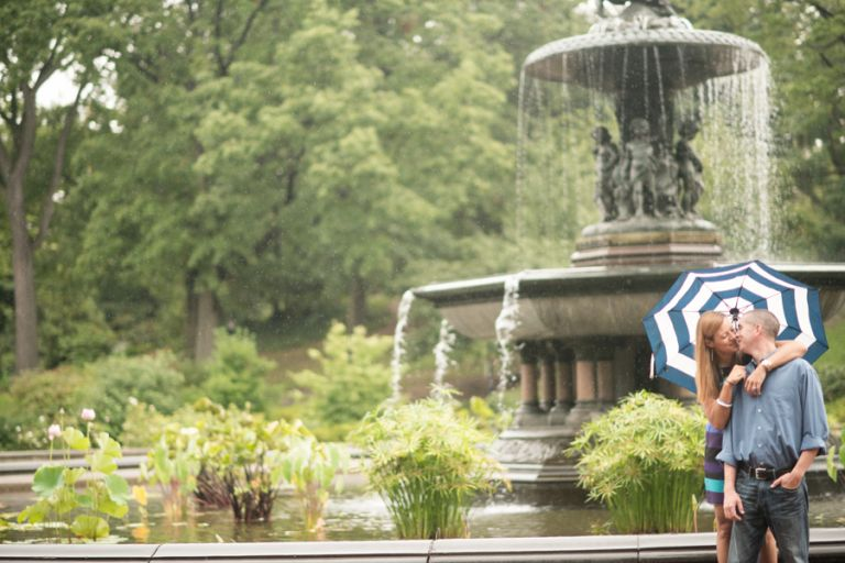 Erin and Tim pose with an umbrella by a fountain during their rainy engagement session in Central Park with Ben Lau Photography.
