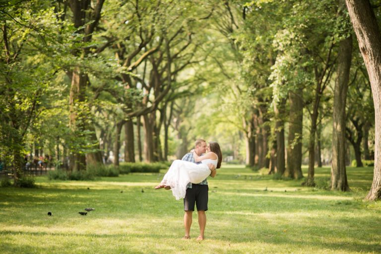 Tim poses with Kathleen in a lawned area during their engagement session in New York City's Central Park. Captured by Ben Lau Photography.