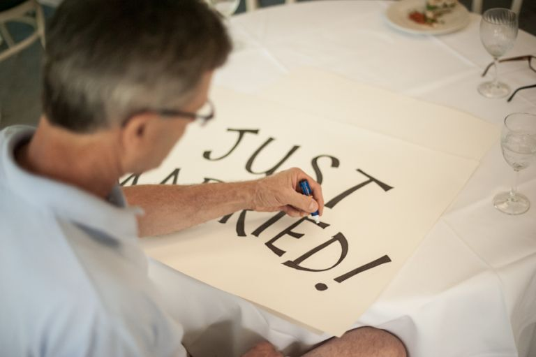 Father of bride prepares signs for Katie and Jason's wedding day at Ram's Head Inn on Shelter Island, NY. Captured by Northern NJ wedding photographer Ben Lau.