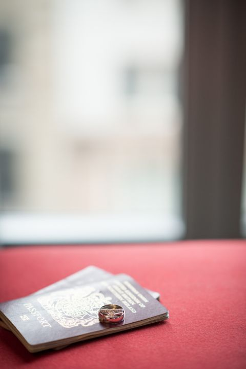 Rings and passport by the hotel window ont he morning of Leeander and Ben's New York City Hall Wedding. Captured by northern NJ wedding photographer Ben Lau.
