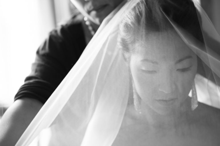 Bride Sarah puts on her veil on her wedding day at The Manor in West Orange, NJ. Captured by northern nj wedding photographer Ben Lau.