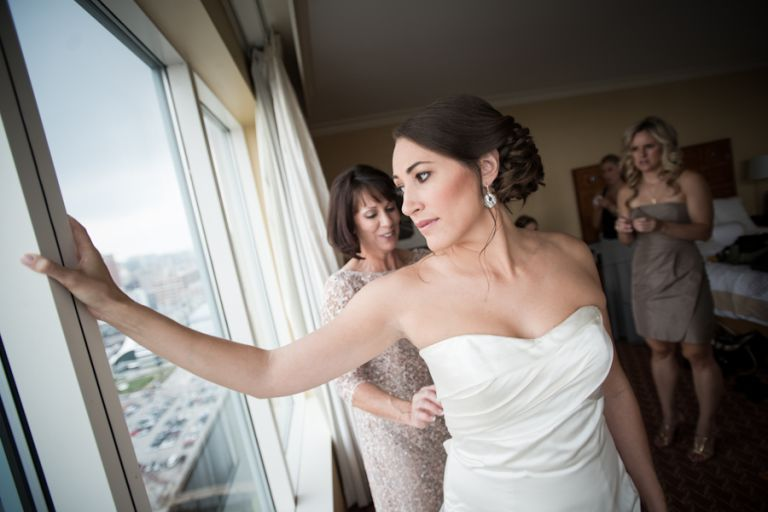 Bride Lisa looks out the window while her mother helps her into her dress on the morning of her wedding at the Baltimore Museum of Industry. Captured by Ben Lau Photography.