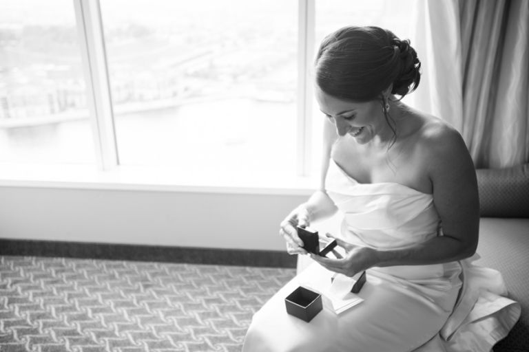 Bride opens her gift on the morning of her wedding at the Baltimore Museum of Industry in Baltimore, MD. Captured by northern NJ wedding photographer Ben Lau.