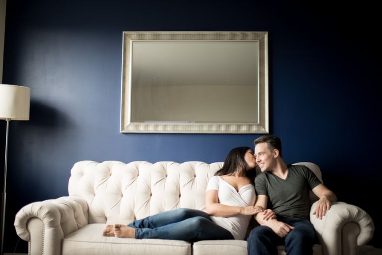 Amedea and Ray cozy up on their couch during their indoor engagement session with NYC wedding photographer Ben Lau.