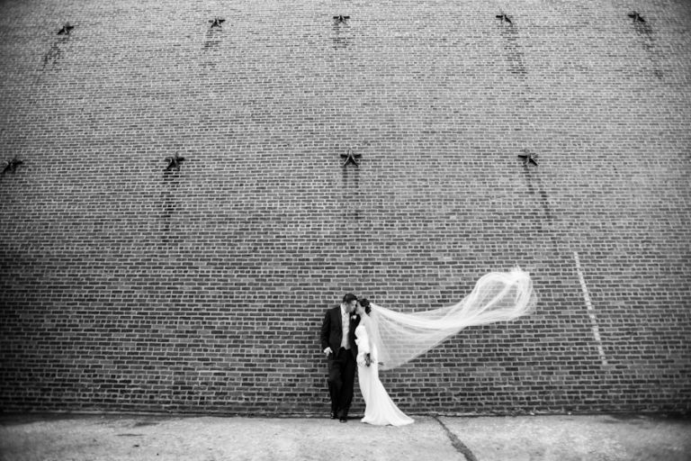 Bride and groom pose along a wall in Red Hook, Brooklyn during their bridal portraits by Ben Lau Photography.