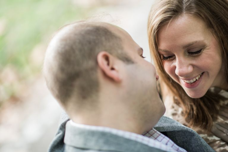 Katie and Craig smile at each other during their engagement session in Central Park with NYC wedding photographer Ben Lau.