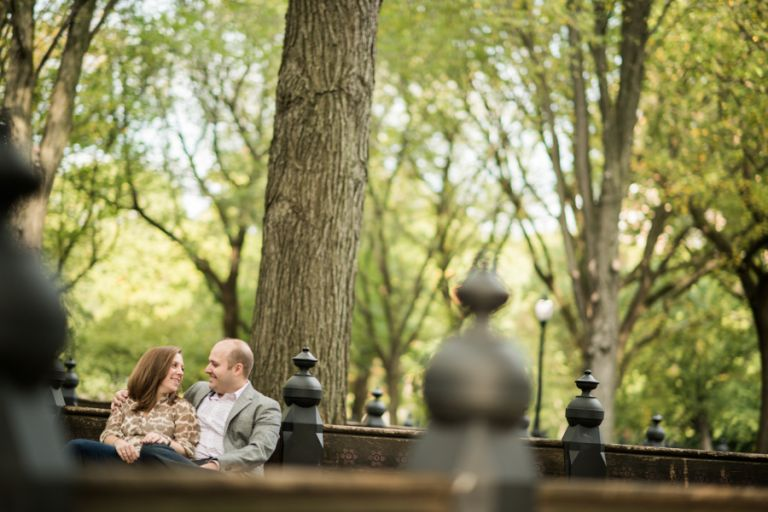 Katie and Craig sit on a bench together during their engagement session in Central Park with NYC wedding photographer Ben Lau.