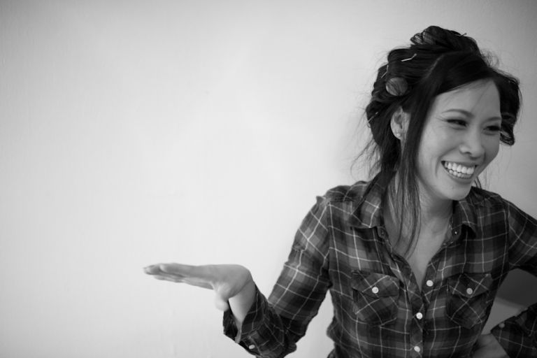 Bride laughs on the morning of her wedding in Brooklyn, NY. Captured by Ben Lau Photography.