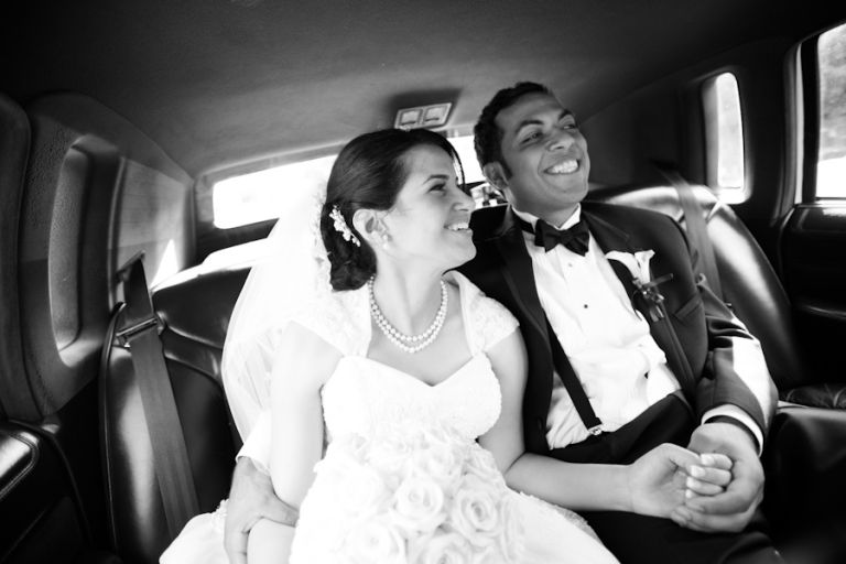Bride laughs in the limo ride to her wedding reception in NJ. Captured by Ben Lau Photography.