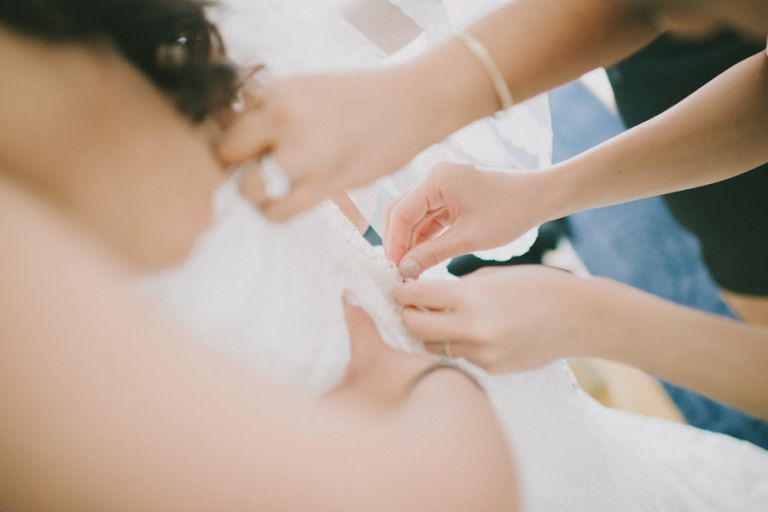 Bride puts on her wedding dress at the Bryant Park Hotel, NY. Captured by NYC wedding photographer Ben Lau.