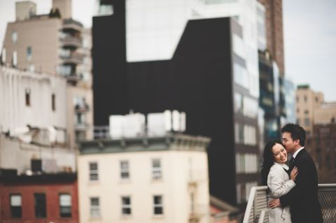 Couple pose against a railing during their engagement session in NYC. Captured by NYC wedding photographer Ben Lau.