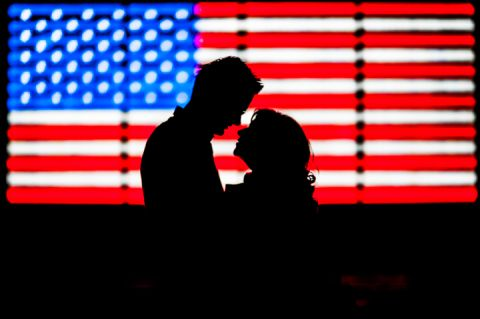 Silhouette of couple kissing in front of American Flag in Times Square during their engagement session.