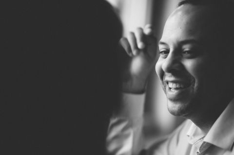 Guy smiles in a coffee shop in Jersey City during an engagement session with NYC wedding photographer Ben Lau.