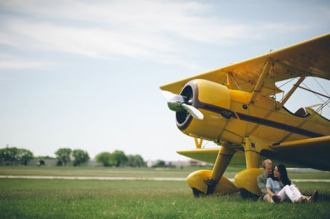Couple sits against a biplane during their engagement session at an airfield in Philadelphia, PA. Captured by NJ wedding photographer Ben Lau.